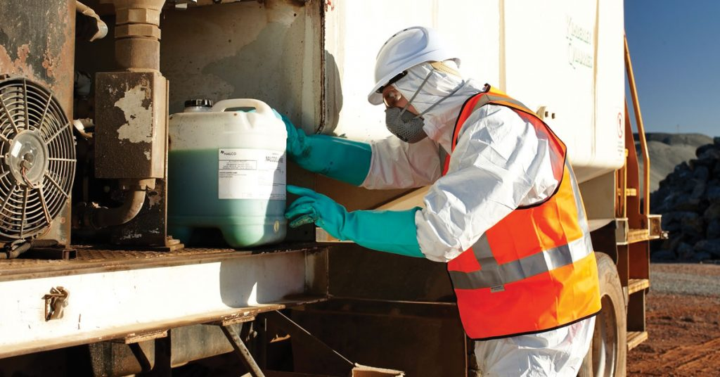 Man with white protective suit on and high-visibility vest examines chemicals with protective gloves on.